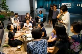 A group of people sitting around a woman who is presenting something in a living room setting.