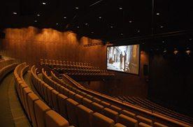 Ein Theatersaal mit mehreren Sitzreihen und einer großen Leinwand im Halbdunkel