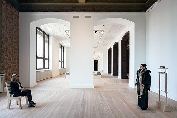 Eine Opernsängerin singt im weitläufigen Ausstellungsraum, während ihr eine einzelne Person gegenübersitzt