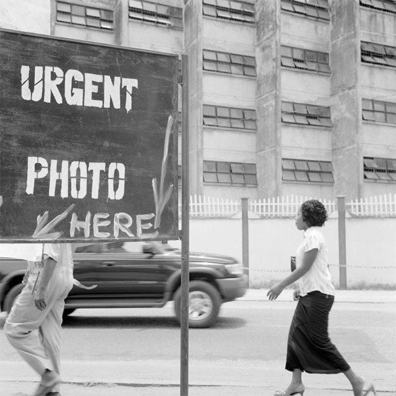 """Schwarzweißfotografie einer Straßenszene: Zu sehen ist eine Frau, die die Straße entlang geht, sowie ein großes Schild, auf dem die Worte """"Urgent Photo Here"""" geschrieben stehen"""